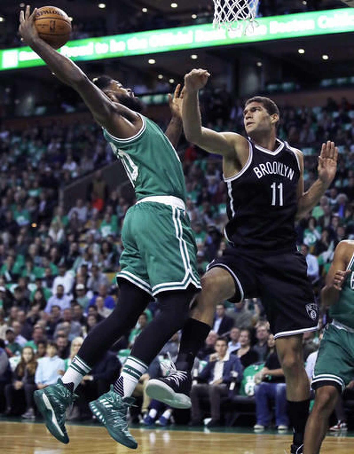 Boston Celtics forward Amir Johnson, left, grabs a rebound over Brooklyn Nets center Brook Lopez (11) during the first quarter of an NBA basketball game in Boston, Wednesday, Oct. 26, 2016. (AP Photo/Charles Krupa)