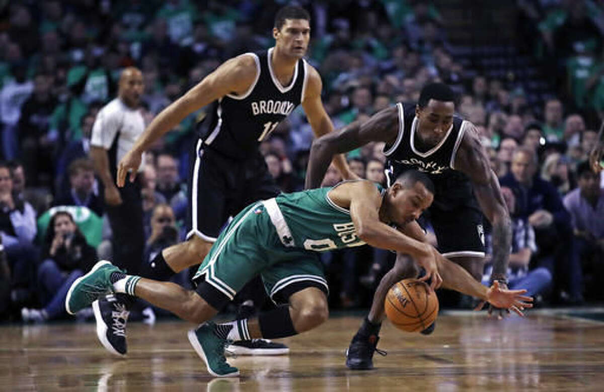 Boston Celtics guard Avery Bradley (0) dives to control a loose ball against Brooklyn Nets guard Rondae Hollis-Jefferson, right, during the first quarter of an NBA basketball game in Boston, Wednesday, Oct. 26, 2016. At rear is Nets center Brook Lopez. (AP Photo/Charles Krupa)