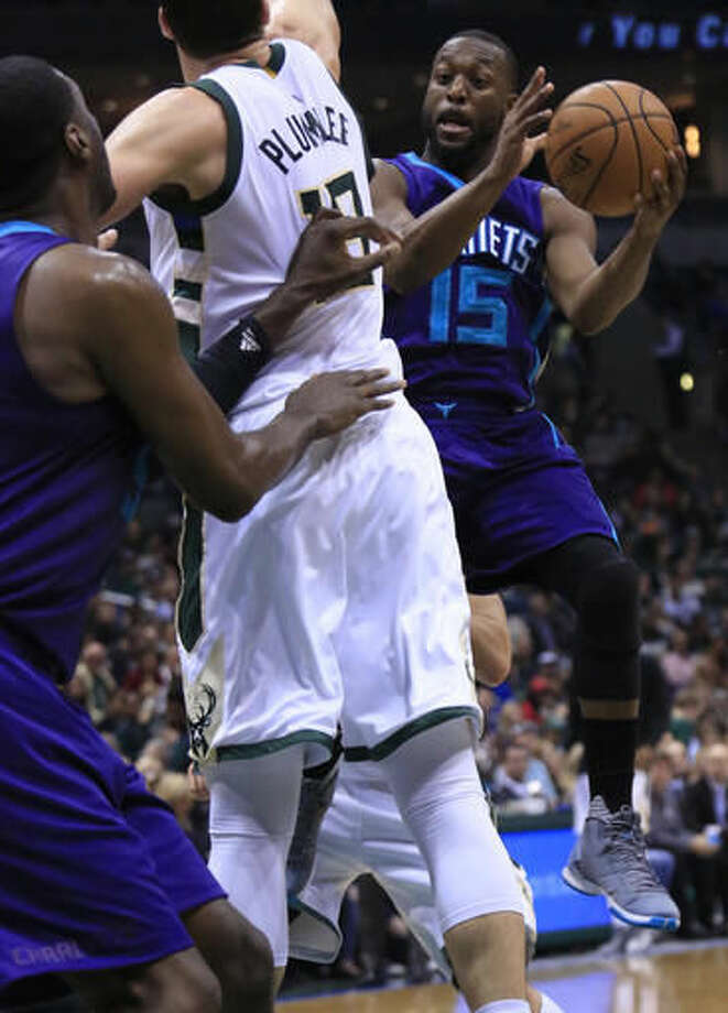 Charlotte Hornets guard Kemba Walker, right, passes the ball around Milwaukee Bucks center Miles Plumlee, left, during the first half of an NBA basketball game Wednesday, Oct. 26, 2016, in Milwaukee. (AP Photo/Darren Hauck)