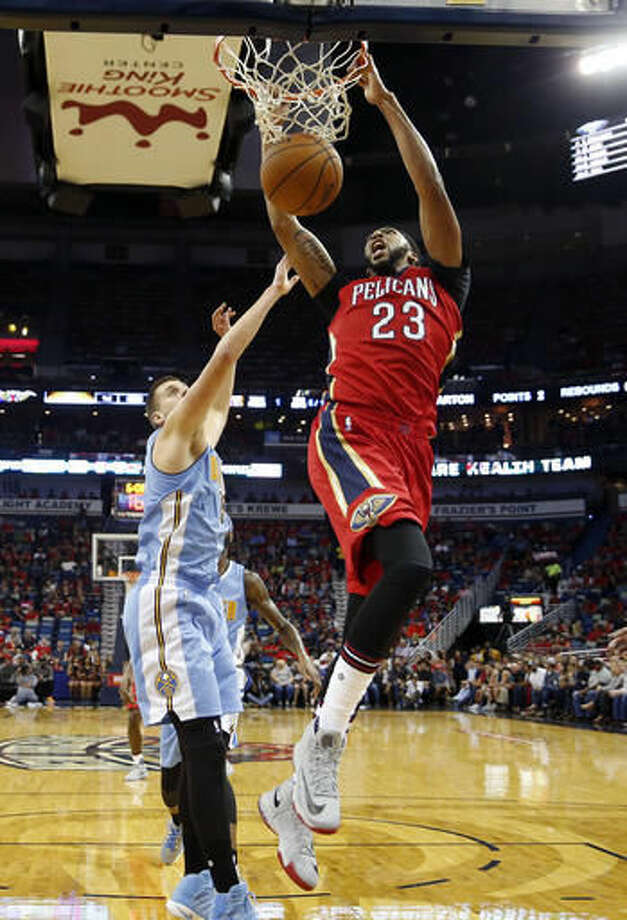 New Orleans Pelicans forward Anthony Davis (23) slam dunks over Denver Nuggets center Nikola Jokic (15) in the first half of an NBA basketball game in New Orleans, Wednesday, Oct. 26, 2016. (AP Photo/Gerald Herbert)
