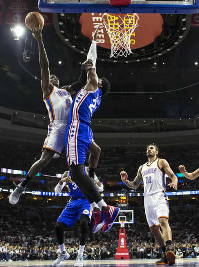 Oklahoma City Thunder's Victor Oladipo, left, goes up for the shot with Philadelphia 76ers' Joel Embiid, right, defending the basket during the first half of an NBA basketball game, Wednesday, Oct. 26, 2016, in Philadelphia. (AP Photo/Chris Szagola)