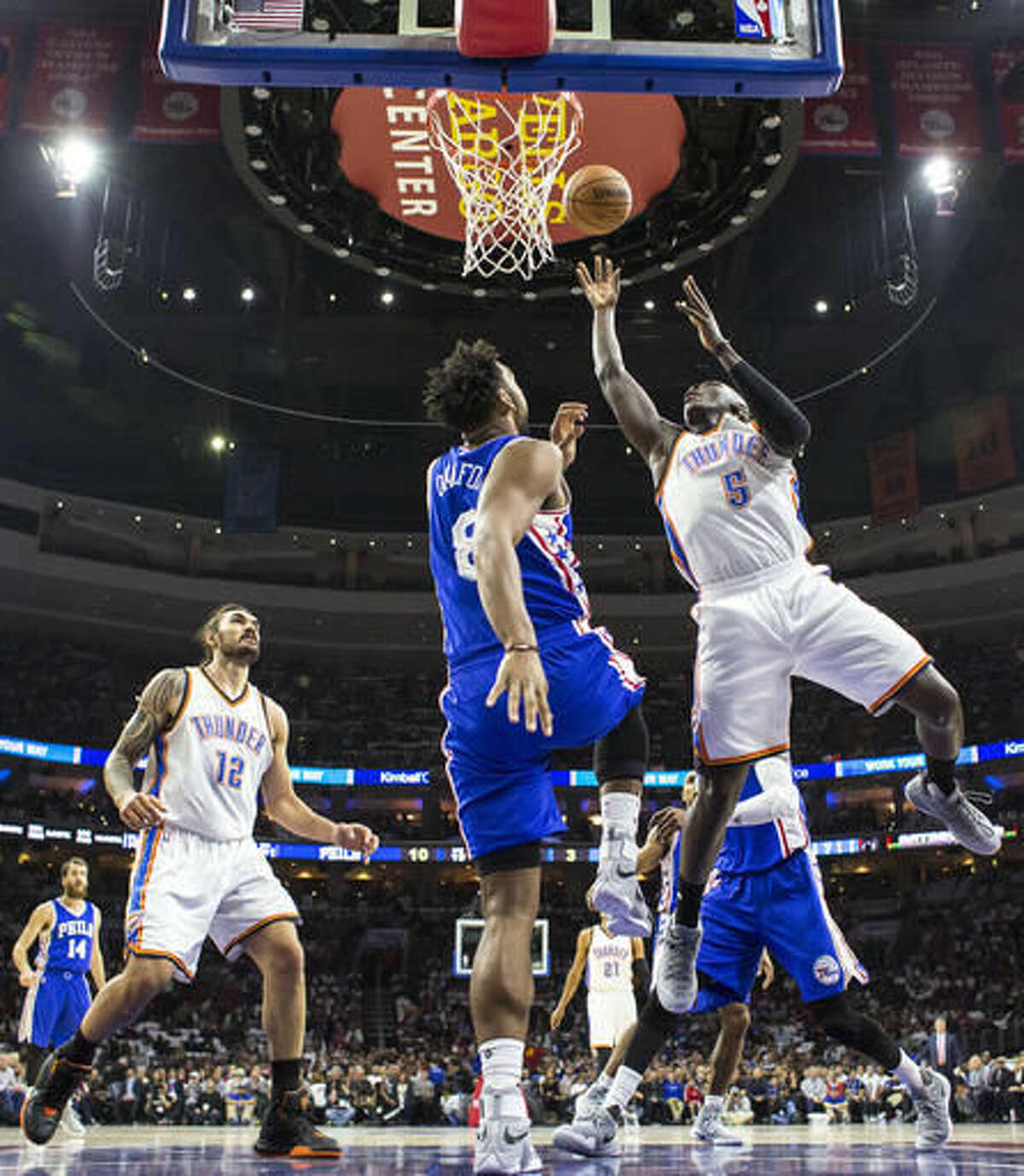 Oklahoma City Thunder's Victor Oladipo, right, puts up the shot with Philadelphia 76ers' Jahlil Okafor, left, defending during the first half of an NBA basketball game, Wednesday, Oct. 26, 2016, in Philadelphia. (AP Photo/Chris Szagola)