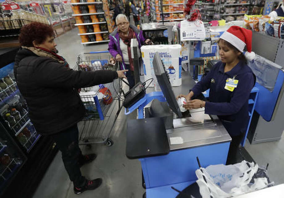In this Wednesday, Oct. 26, 2016, photo, Gladys Ortega, left, and Ursula Polano, center, both from Paterson, N.J., check out at the register of Dimpal Mandania, at Wal-Mart in Teterboro, N.J. Wal-Mart may be known for its every low prices but this holiday season it wants to be known for service too. (AP Photo/Julio Cortez)