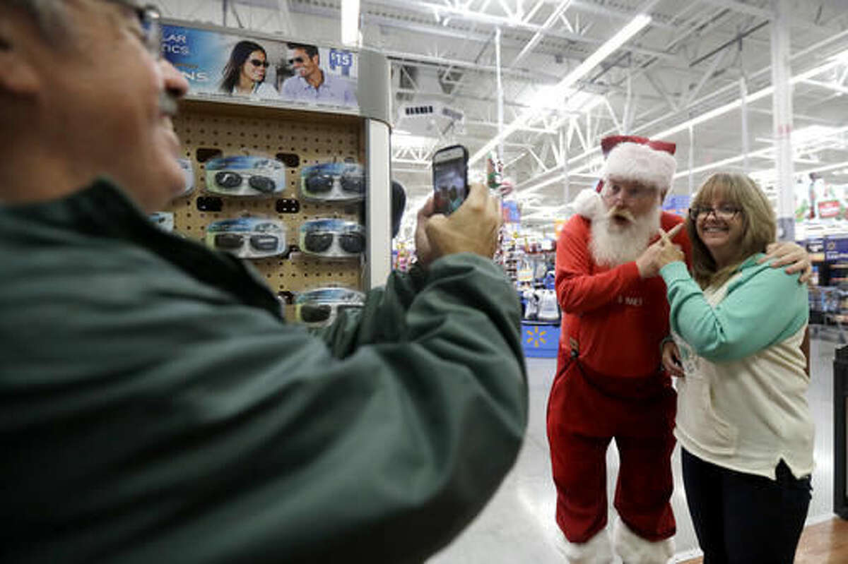 In this Wednesday, Oct. 26, 2016, photo, a man playing the role of Santa Claus, center, and Karyn Ochiuzzo, right, of Wood-Ridge, N.J., pose for a photo taken by Bill Ochiuzzo at Wal-Mart in Teterboro, N.J. Wal-Mart may be known for its every low prices but this holiday season it wants to be known for service too. (AP Photo/Julio Cortez)