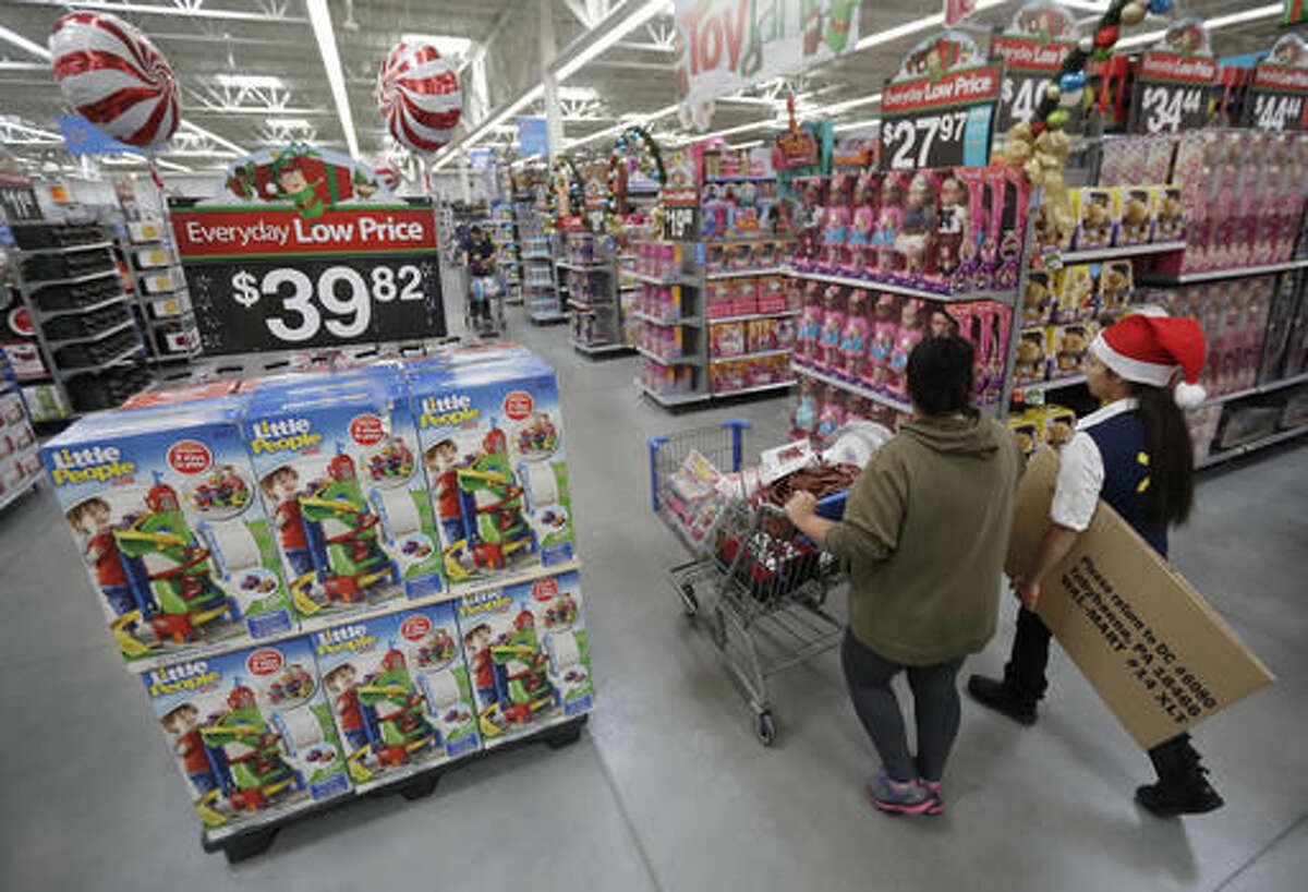 In this Wednesday, Oct. 26, 2016, photo, a shopper, left, walks with a store associate in the toy section at Wal-Mart in Teterboro, N.J. Wal-Mart may be known for its every low prices but this holiday season it wants to be known for service too. (AP Photo/Julio Cortez)