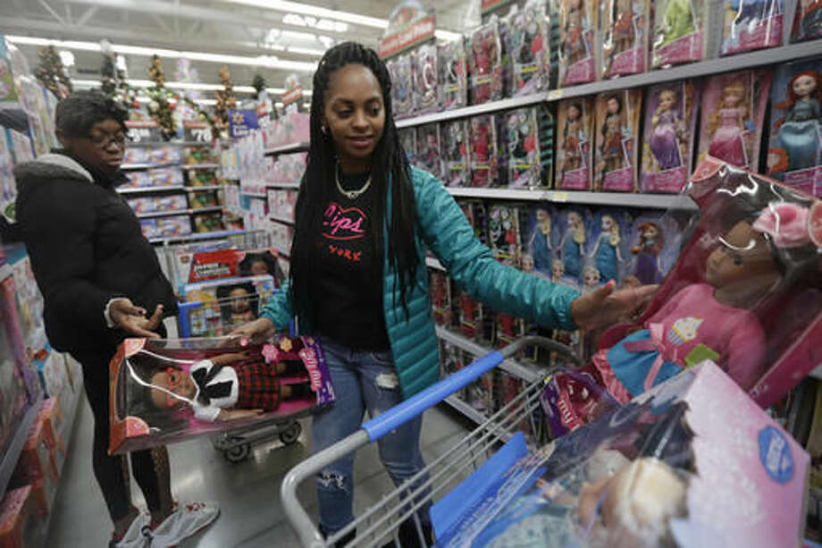 In this Wednesday, Oct. 26, 2016, photo, Tiffany Davis, left, and Choisette Hargon, both of Paterson, N.J., shop for toys ahead of Christmas at a Wal-Mart in Teterboro, N.J. Wal-Mart may be known for its every low prices but this holiday season it wants to be known for service too. (AP Photo/Julio Cortez)