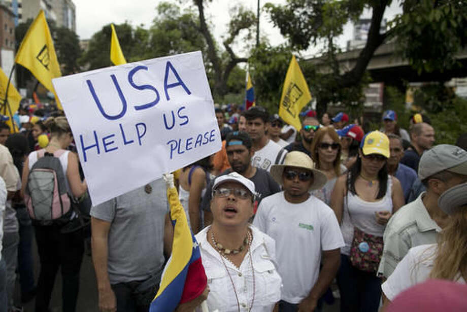 A woman holds up a sign asking for help from the United States during a protest against Venezuela's President Nicolas Maduro in Caracas, Venezuela, Wednesday, Oct. 26, 2016. The opposition protested on the heels of a move by congress to open a political trial against Maduro, whose allies have blocked moves for a recall election. (AP Photo/Alejandro Cegarra)