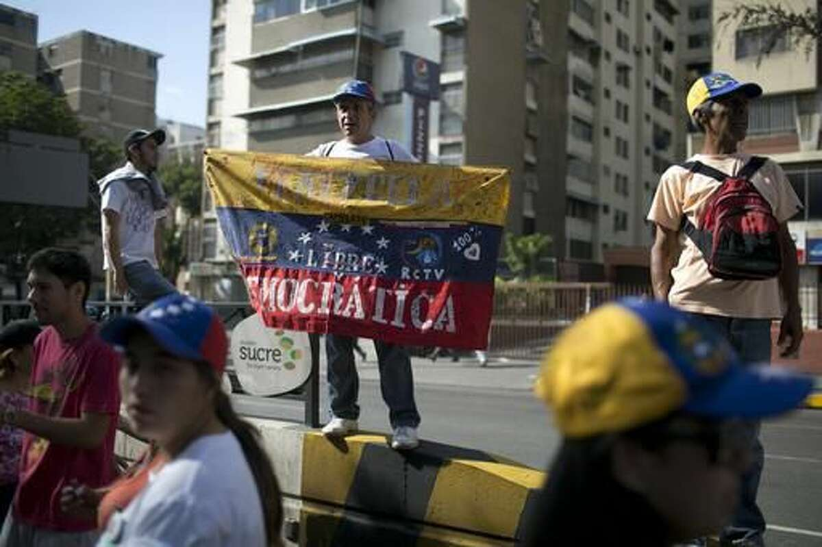 A man holds a flag during a protest against Venezuela's President Nicolas Maduro in Caracas, Venezuela Wednesday, Oct. 26, 2016. The opposition protested on the heels of a move by congress to open a political trial against Maduro, whose allies have blocked moves for a recall election. (AP Photo/Alejandro Cegarra)