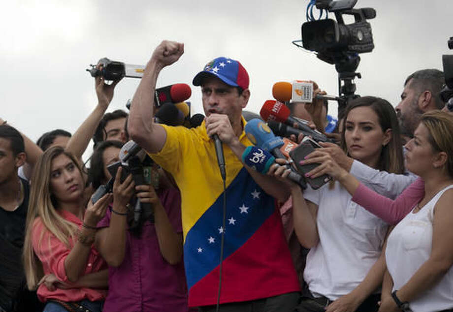 Opposition leader Henrique Capriles addresses protesters during a demonstration against Venezuela's President Nicolas Maduro in Caracas, Venezuela, Wednesday, Oct. 26, 2016. The opposition protested Wednesday on the heels of a move by congress to open a political trial against Maduro, whose allies have blocked moves for a recall election. (AP Photo/Alejandro Cegarra)