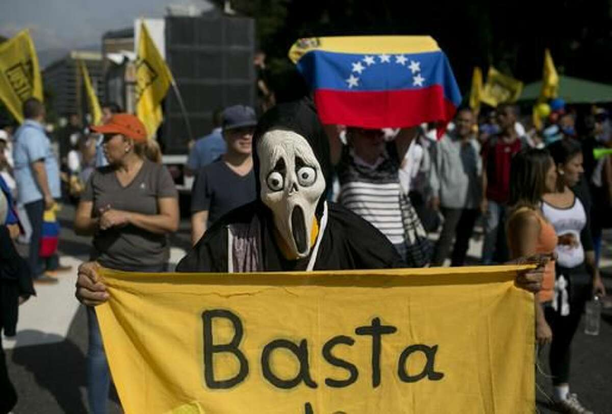 """A protester, wearing a Ghostface mask and holding a banner that reads in Spanish, """"Stop,"""" takes part in a protest against President Nicolas Maduro, in Caracas, Venezuela Wednesday, Oct. 26, 2016. Venezuela's standoff deepened after congress voted to open a political trial against Maduro for breaking the constitutional order and opposition leaders called for mass demonstrations on Wednesday to drive the socialist leader from office. (AP Photo/Alejandro Cegarra)"""