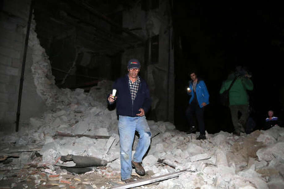 Residents walk past rubble in the village of Visso, central Italy, Wednesday, Oct. 26, 2016 following an earthquake. A pair of powerful aftershocks shook central Italy on Wednesday, knocking out power, closing a major highway and sending panicked residents into the rain-drenched streets just two months after a powerful earthquake killed nearly 300 people. (Matteo Crocchioni/ANSA via AP)