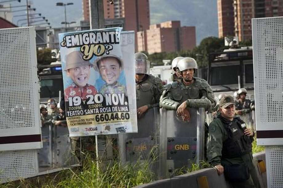 Riot police look at protestors while standing guard next to to a bill promoting a theater presentation during a protest against Venezuela's President Nicolas Maduro in Caracas, Venezuela, Wednesday, Oct. 26, 2016. Venezuela's standoff deepened after congress voted to open a political trial against Maduro for breaking the constitutional order and opposition leaders called for mass demonstrations on Wednesday to drive the leader from office. (AP Photo/Rodrigo Abd)
