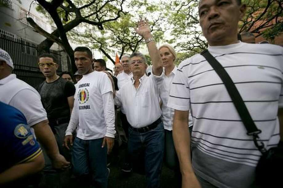 National Assembly President Henry Ramos Allup waves to supporters during a march against Venezuela's President Nicolas Maduro in Caracas, Venezuela, Wednesday, Oct. 26, 2016. The opposition protested on the heels of a move by congress to open a political trial against Maduro, whose allies have blocked moves for a recall election. (AP Photo/Ariana Cubillos)
