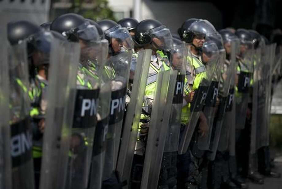 Police block an opposition march against Venezuela's President Nicolas Maduro, along on a main street in Caracas, Venezuela, Wednesday, Oct. 26, 2016. The opposition protested on the heels of a move by congress to open a political trial against Maduro, whose allies have blocked moves for a recall election. (AP Photo/Alejandro Cegarra)