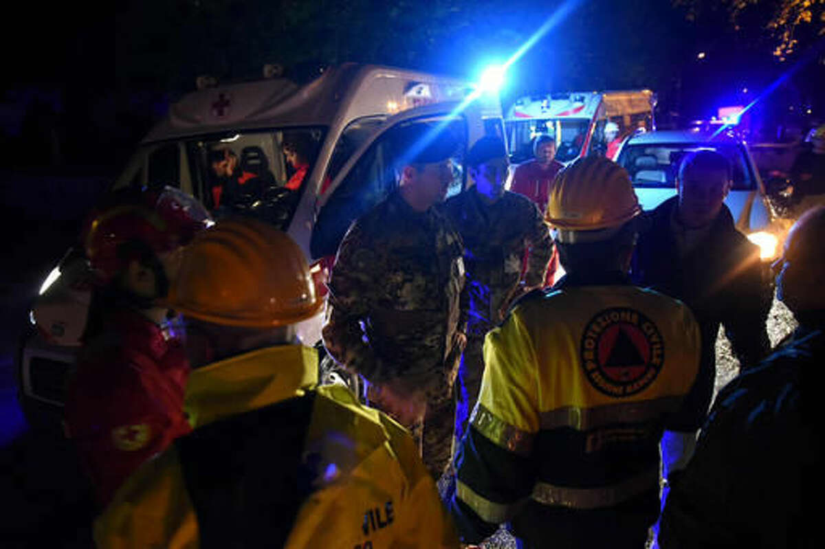 Rescuers gather in the village of Visso, central Italy, Wednesday, Oct. 26, 2016 following an earthquake. A pair of powerful aftershocks shook central Italy on Wednesday, knocking out power, closing a major highway and sending panicked residents into the rain-drenched streets just two months after a powerful earthquake killed nearly 300 people. (Matteo Crocchioni/ANSA via AP)