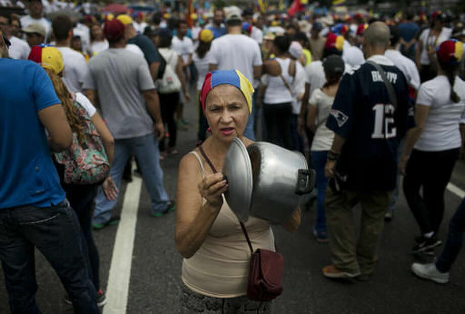 A woman bangs a pot during a protest against Venezuela's President Nicolas Maduro in Caracas, Venezuela, Wednesday, Oct. 26, 2016. Masses of protesters jammed the streets of Venezuela's capital on the heels of a move by congress to open a political trial against Maduro, whose allies have blocked moves for a recall election. (AP Photo/Alejandro Cegarra)