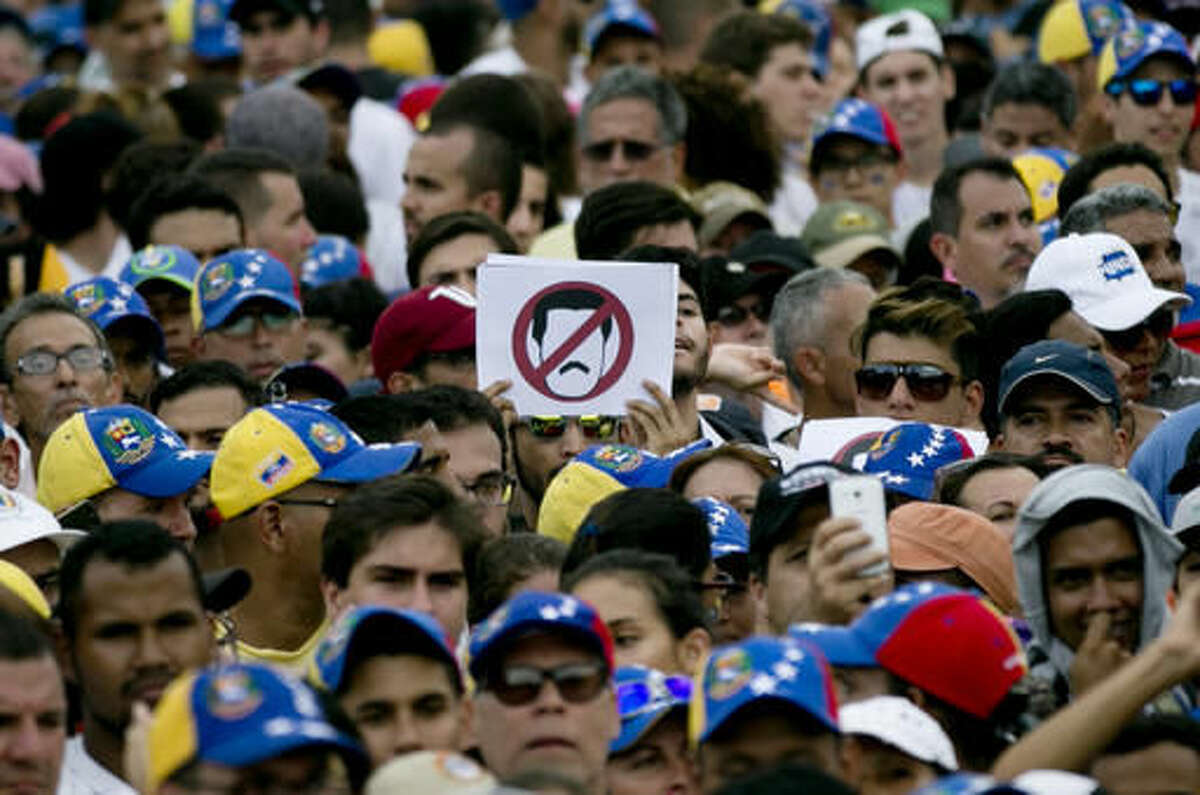 People protest against Venezuela's President Nicolas Maduro in Caracas, Venezuela, Wednesday, Oct. 26, 2016. The opposition protested on the heels of a move by congress to open a political trial against Maduro, whose allies have blocked moves for a recall election. (AP Photo/Ariana Cubillos)