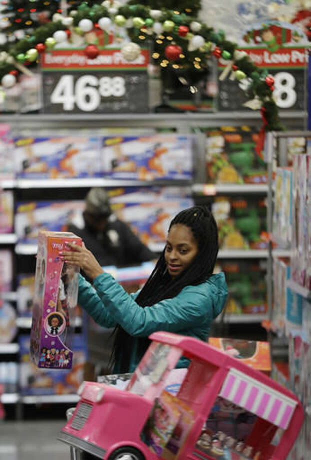 In this Wednesday, Oct. 26, 2016, photo, Choisette Hargon, of Paterson, N.J., shops for toys ahead of Christmas at Wal-Mart in Teterboro, N.J. Wal-Mart may be known for its every low prices but this holiday season it wants to be known for service too. (AP Photo/Julio Cortez)