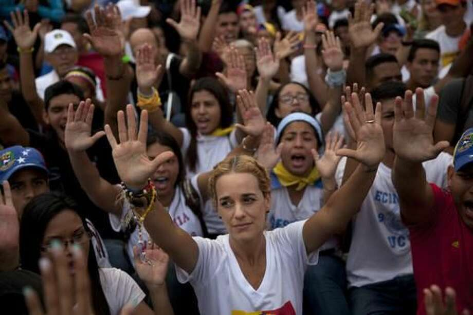 Lilian Tintori, center, wife of jailed opposition leader Leopoldo Lopez, talkes part in a protest against Venezuela's President Nicolas Maduro in Caracas, Venezuela, Wednesday, Oct. 26, 2016. Anti-government protesters jammed the streets of Venezuela's capital on the heels of a decision by congress to open a political trial against President Nicolas Maduro, whose allies have blocked moves for a recall election. (AP Photo/Rodrigo Abd)