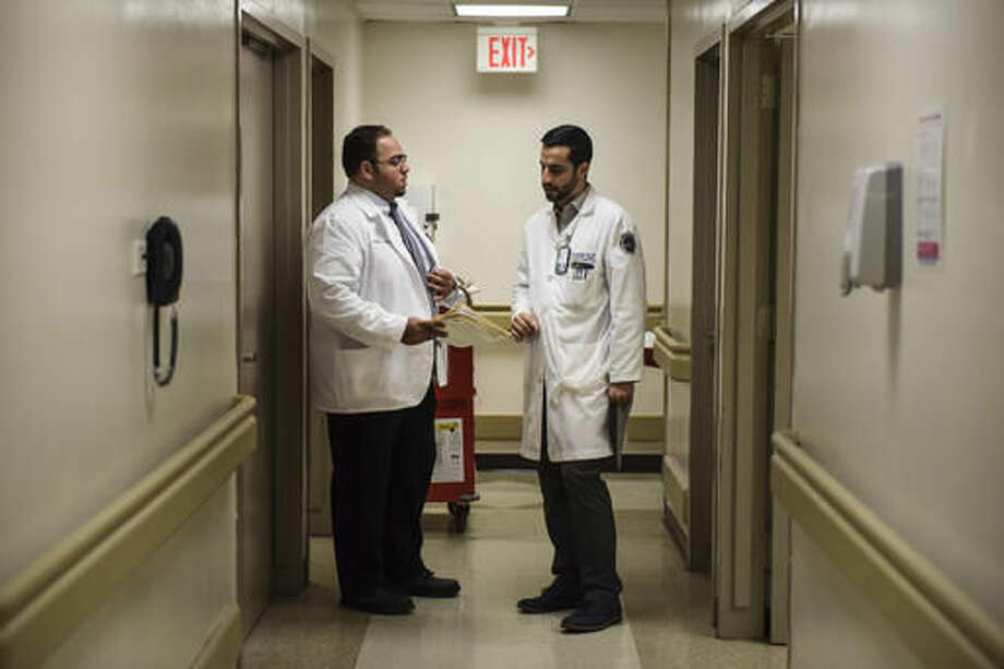 In this Oct. 24, 2016 photo, resident physician Eric Hernandez Ortiz, right, talks with a colleague at the Medical Center orthopedic clinic in San Juan, Puerto Rico. Doctors have gradually left Puerto Rico during a decade-long recession that has gripped the island and driven more than 200,000 people to the U.S. mainland seeking better opportunities. (AP Photo/Carlos Giusti)