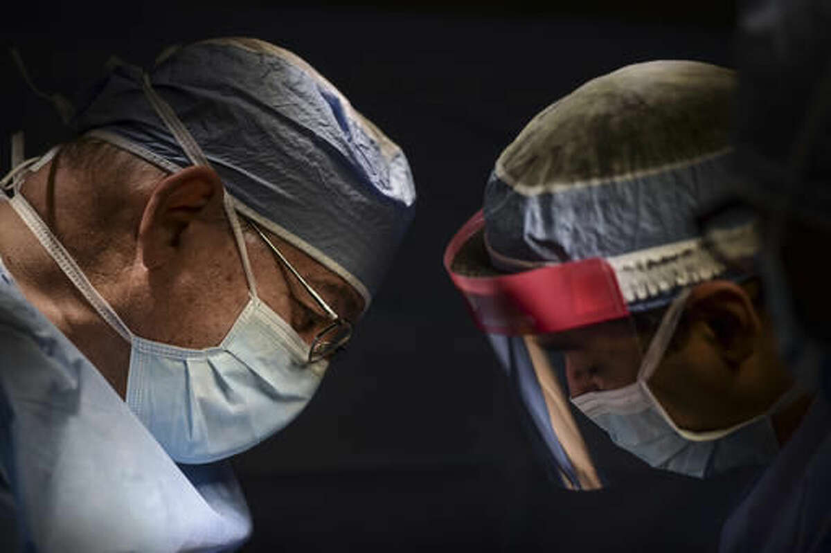 In this In this Oct. 7, 2016 photo, Dr. Reynold Lopez, left, a surgical oncologist, works hand in hand with resident physician Edgardo Cintron, during a thyroid surgery at Dr. Isaac González Martínez Oncological Hospital in San Juan, Puerto Rico. Many specialists no longer accept patients with Medicaid, which covers roughly half of Puerto Rico's population. (AP Photo/Carlos Giusti)