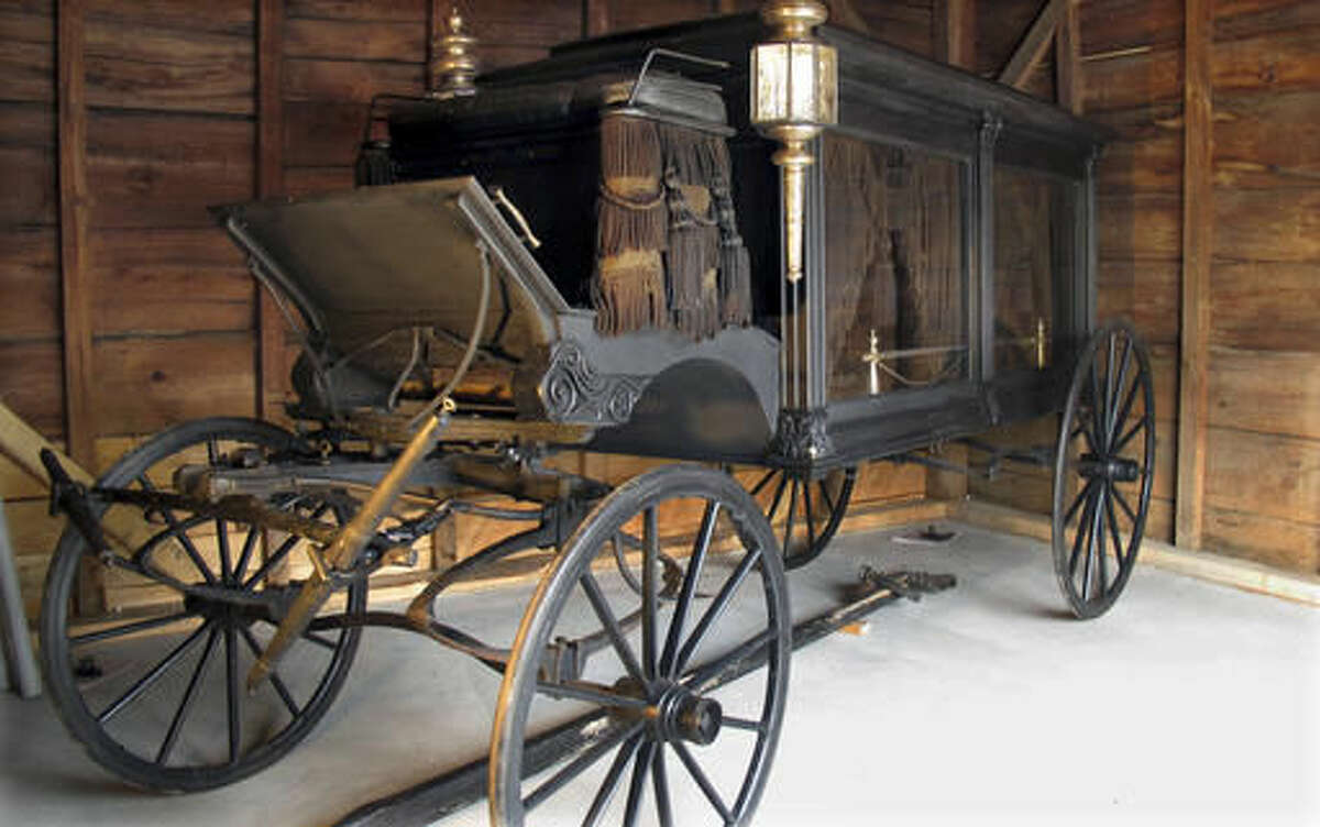 In this Oct. 18, 2016 photo, the town hearse is housed in the recently renovated town hearse house at the entrance to the Brookside Cemetery in Chester, Vt. The adjacent town tomb also was renovated. Horse-drawn hearses were once ordinary in villages across the region. They were kept in