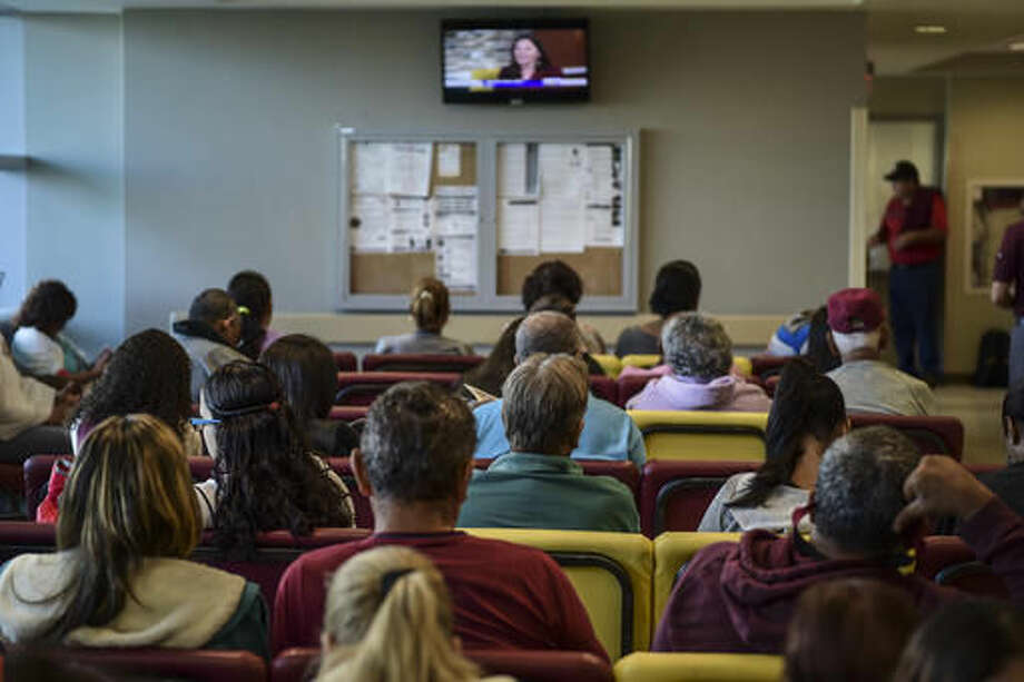 In this Oct. 24, 2016 photo, patients wait for their turn at one of the Medical Center external clinics in San Juan, Puerto Rico. The exodus of doctors to the United States in search of better wages is one of the main factors linked to the current shortage of specialists in the Island. (AP Photo/Carlos Giusti)