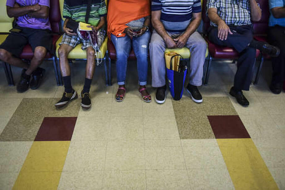 In this Oct. 24, 2016 photo, patients wait their turn at one of the Medical Center external clinics in San Juan, Puerto Rico. A steady departure of medical specialists from Puerto Rico has turned into a stampede amid the island's ongoing economic crisis leaving patients with few doctors to take care of their ills. (AP Photo/Carlos Giusti)