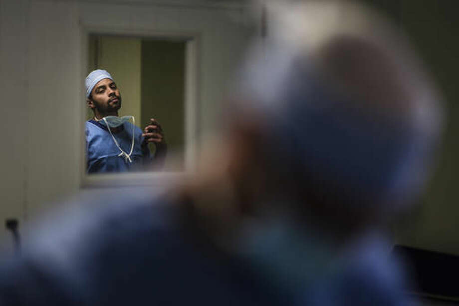 In this Oct. 7, 2016 photo, Miguel Perez, an intern student from the University of Puerto Rico School of Medicine, puts away his cell phone before walking into the operating room at the Dr. Isaac González Martínez Oncological Hospital in San Juan, Puerto Rico. Once they complete their general surgery training, many residents are moving to the United States in search of better wages, one of the main factors linked to the current shortage of specialists in the Island. (AP Photo/Carlos Giusti)