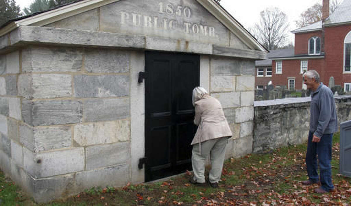 In this Oct. 18, 2016 photo, Lillian Willis, left, with Hans Forlie, right, prepares to open the town tomb at the Brookside Cemetery in Chester, Vt. The small town of Chester has restored its 1830s-era hearse house, now home to its last horse-drawn hearse, purchased in 1907. Together with the 1850 town tomb, they will become part of a permanent display about how the town once cared for its dead. (AP Photo/Wilson Ring)