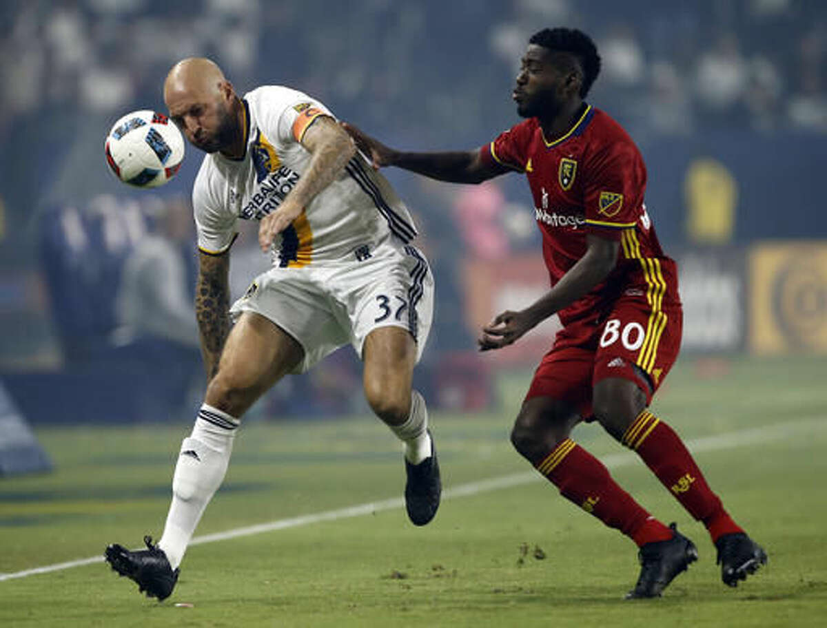 Los Angeles Galaxy defender Jelle Van Damme, left, protects the ball from Real Salt Lake forward Olmes Garcia, right, during the first half of a knockout round MLS playoff soccer match in Carson, Calif., Wednesday, Oct. 26, 2016. (AP Photo/Alex Gallardo)