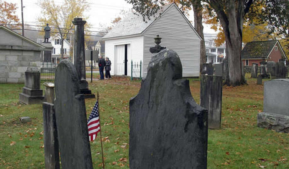 In this Oct. 18, 2016 photo, the hearse house, center, and town tomb, left, stand at the entrance to the Brookside Cemetery in Chester, Vt.. The small town of Chester has restored its 1830s-era hearse house, now home to its last horse-drawn hearse, purchased in 1907. Together with the 1850 town tomb, they will become part of a permanent display about how the town once cared for its dead. (AP Photo/Wilson Ring)
