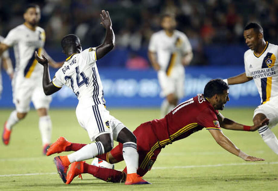 Los Angeles Galaxy midfielder Ema Boateng (24) fouls Real Salt Lake midfielder Javier Morales (11) in the box for a penalty kick during the first half of a knockout round MLS playoff soccer match in Carson, Calif., Wednesday, Oct. 26, 2016. (AP Photo/Alex Gallardo)