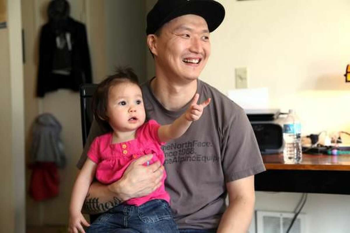 FILE - In this March 19, 2015, file photo, Korean adoptee Adam Crapser poses with daughter, Christal, 1, in the family's living room in Vancouver, Wash. Crapser, a South Korean man who was flown to the U.S. 37 years ago and adopted by an American couple at age 3 has been ordered deported back to a country that is completely alien to him, Wednesday, Oct. 26, 2016.(AP Photo/Gosia Wozniacka, file)