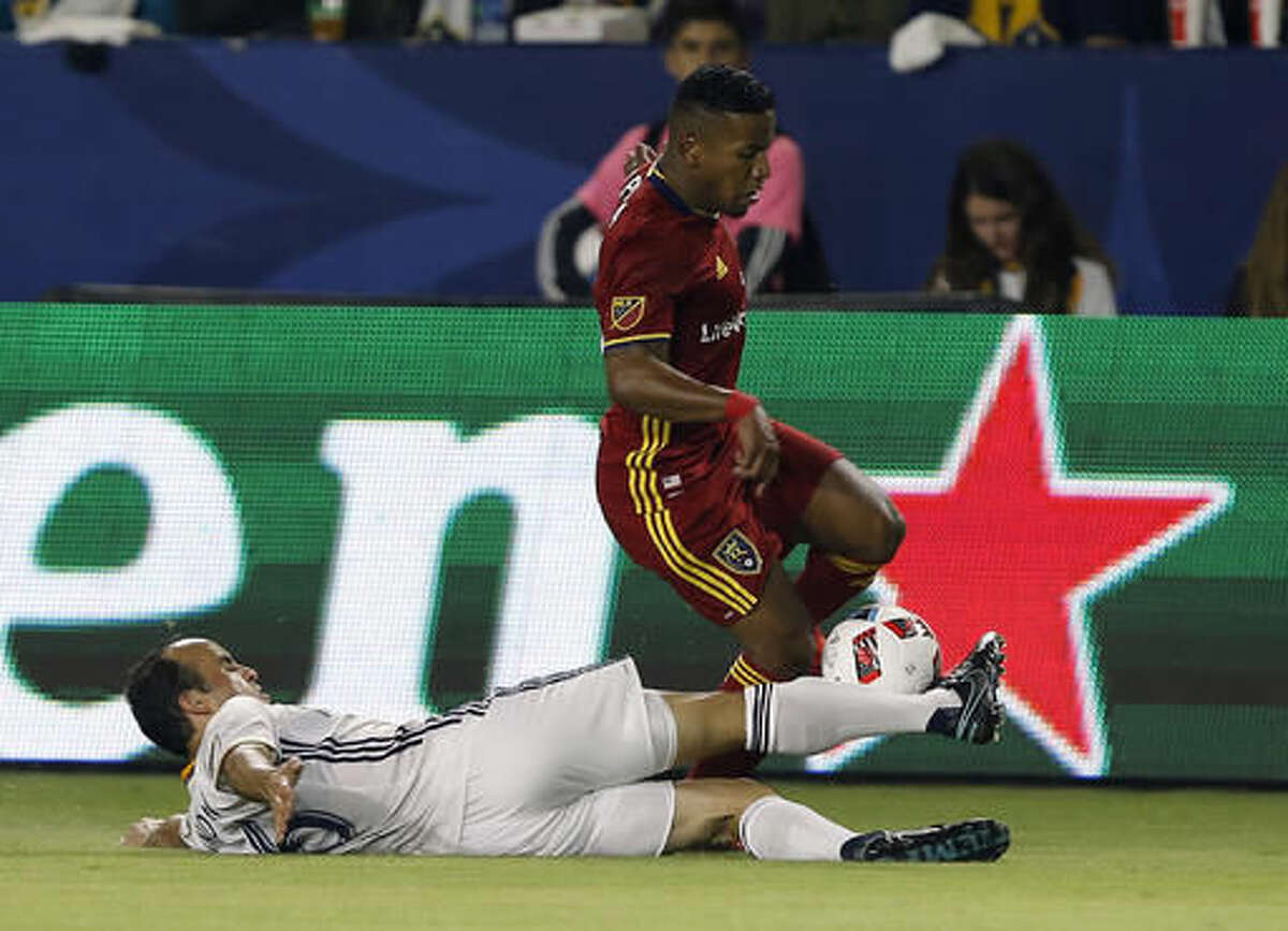 Los Angeles Galaxy forward Landon Donovan, left, slides to tackle the ball away from Real Salt Lake forward Joao Plata, right, during the first half of a knockout round MLS playoff soccer match in Carson, Calif., Wednesday, Oct. 26, 2016. (AP Photo/Alex Gallardo)