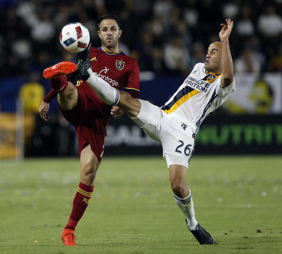 Real Salt Lake forward Juan Martinez, left, battles Los Angeles Galaxy forward Landon Donovan, right, for the ball during the first half of a knockout round MLS playoff soccer match in Carson, Calif., Wednesday, Oct. 26, 2016. (AP Photo/Alex Gallardo)