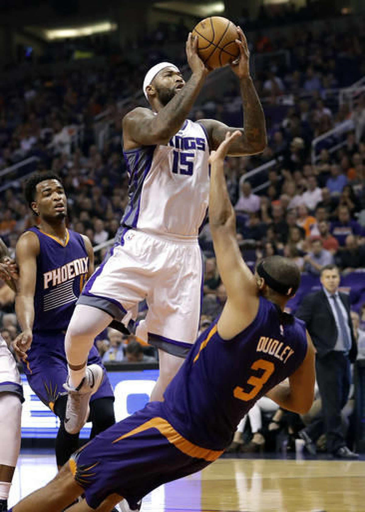 Sacramento Kings center DeMarcus Cousins (15) fouls Phoenix Suns forward Jared Dudley (3) during the first half of an NBA basketball game, Wednesday, Oct. 26, 2016, in Phoenix. (AP Photo/Matt York)