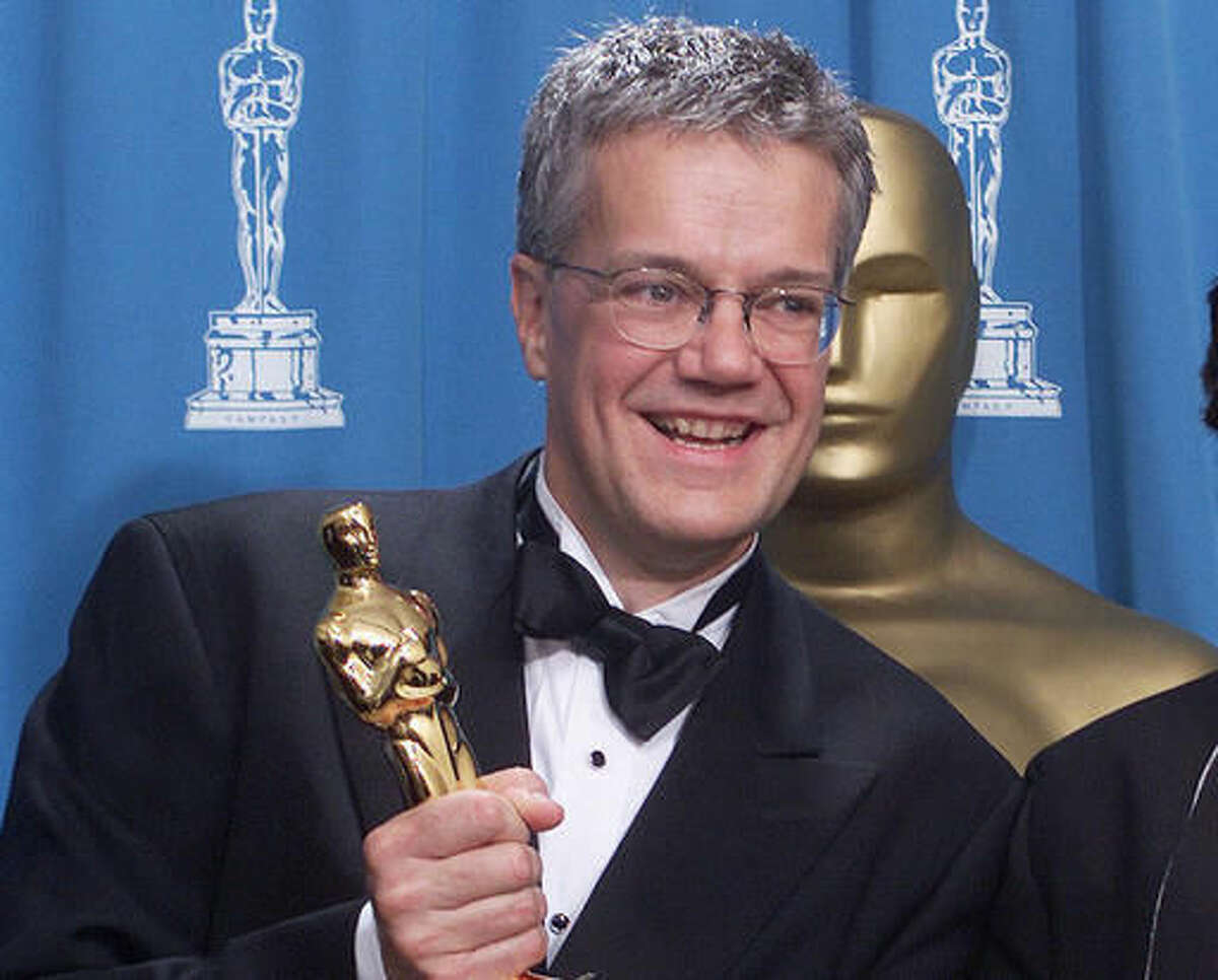 """FILE - In this March 25, 2001, file photo, Rob Cook poses backstage with Loren Carpenter, not seen, with his Oscar for significant advancements to the field of motion picture rendering as exemplified in Pixar's """"Renderman,"""" at the 73rd annual Academy Awards in Los Angeles. Cook is taking over a U.S. government agency responsible for improving federal digital technology. After more than four decades in the private sector, Cook will become commissioner of the Technology Transformation Service on Oct. 31. He will have top secret security clearance. (AP Photo/Richard Drew, File)"""