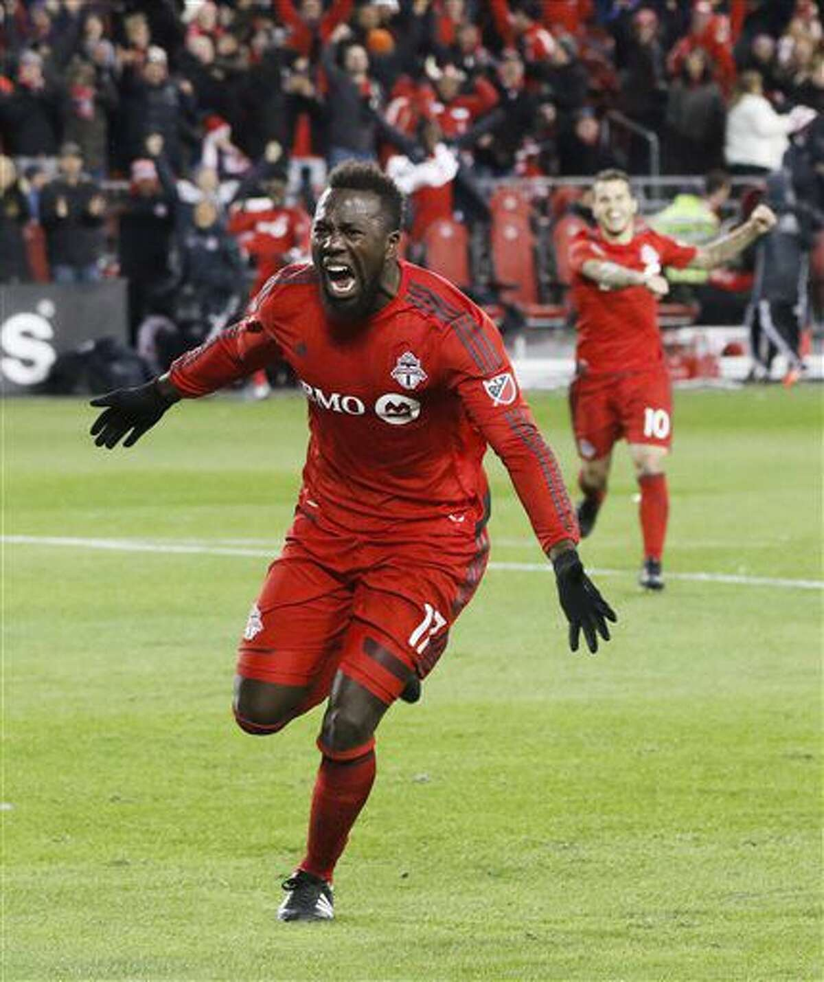 Toronto FC's Jozy Altidore celebrates his goal in front of Sebastian Giovinco, right, against the Philadelphia Union during the second half of an MLS soccer playoff match in Toronto, Wednesday, Oct. 26, 2016. (Mark Blinch/The Canadian Press via AP)