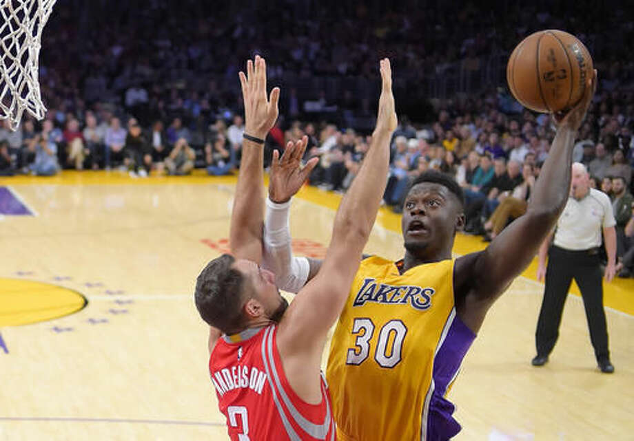 Los Angeles Lakers forward Julius Randle, right, shoots a s Houston Rockets forward Ryan Anderson defends during the first half of an NBA basketball game, Wednesday, Oct. 26, 2016, in Los Angeles. (AP Photo/Mark J. Terrill)