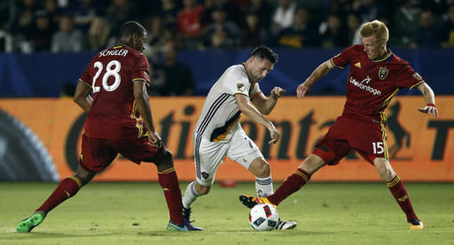 Los Angeles Galaxy forward Robbie Keane, center, tries to split between Real Salt Lake forward Chris Schuler, left, and defender Justen Glad, right, during the second half of a knockout round MLS playoff soccer match in Carson, Calif., Wednesday, Oct. 26, 2016. Galaxy won 3-1. (AP Photo/Alex Gallardo)
