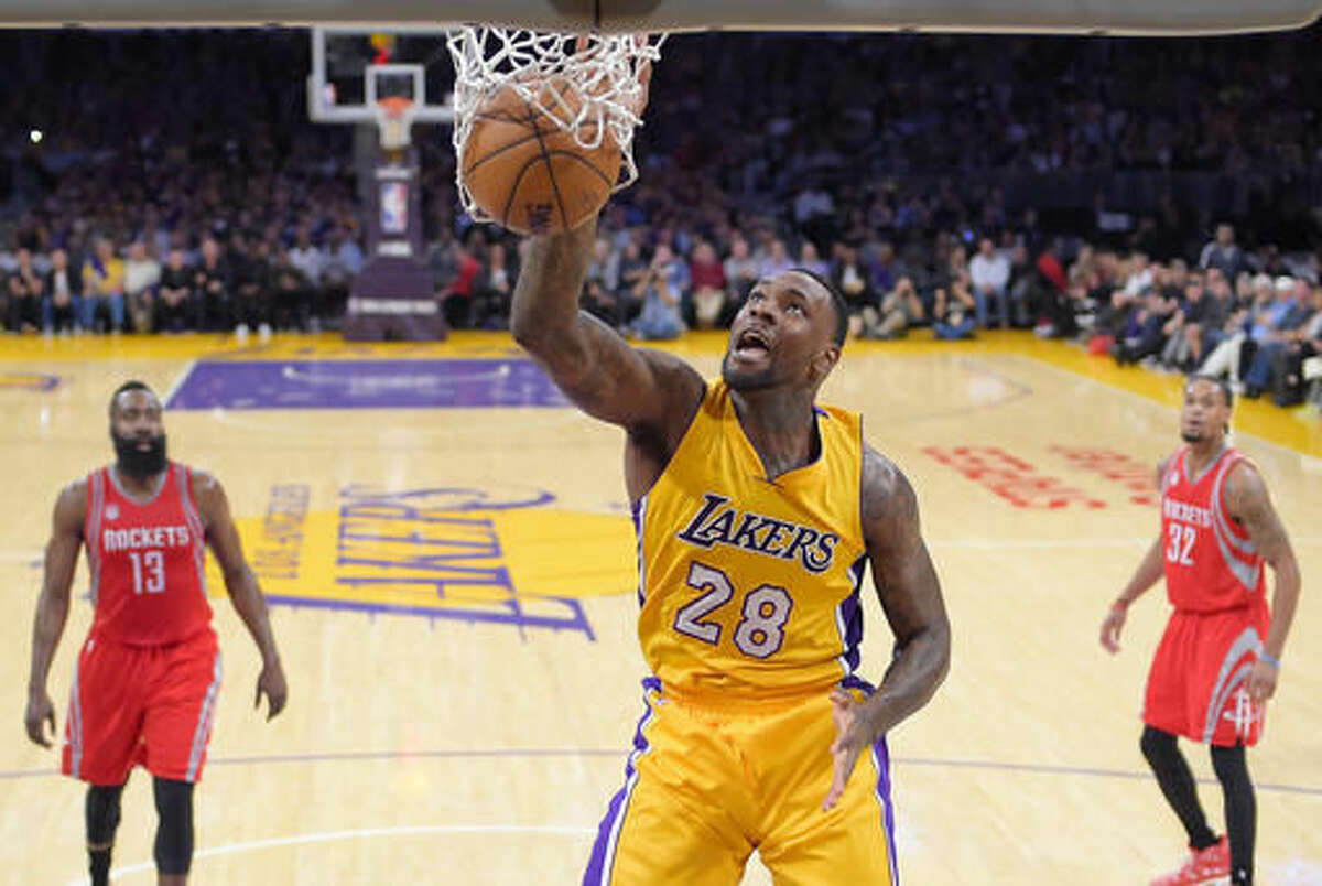 Los Angeles Lakers center Tarik Black, center, punks as Houston Rockets guard James Harden, left, and guard K.J. McDaniels watches during the first half of an NBA basketball game, Wednesday, Oct. 26, 2016, in Los Angeles. (AP Photo/Mark J. Terrill)