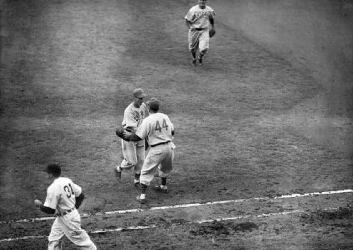 FILE - In this Oct., 3, 1945, file photo, Phil Cavarretta (44), of the Chicago Cubs, rushes over from first base to pitcher Hank Borowy to congratulate him on his six-hit, 9-0, victory over the Detroit Tigers in Game 1 of baseball's World Series in Detroit, Mich. (AP Photo/File)