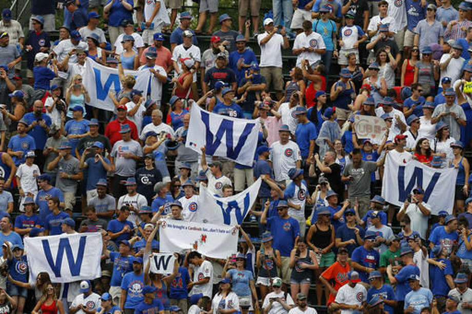 FILE - In this Aug. 12, 2016 file photo, fans fly their W flags as the Chicago Cubs defeated the St. Louis Cardinals 13-2 in a baseball game at Wrigley Field in Chicago. Not since Oct. 10, 1945, has a World Series game been played at Wrigley Field in Chicago. As the World Series shifts to Chicago this weekend, all eyes are on the second-oldest ballpark in the major leagues. (Brian Hill/Daily Herald via AP File)