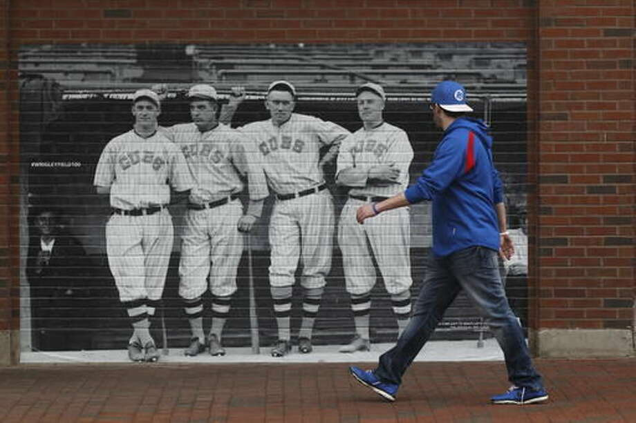 FILE - In this April 10, 2014 file photo, a life size archival photo is displayed on the outside of the left field wall along Waveland Avenue to showcase the 100th anniversary of Wrigley Field as fans arrive at the ballpark before a baseball game between Pittsburgh Pirates and Chicago Cubs in Chicago. Not since Oct. 10, 1945, has a World Series game been played at Wrigley Field in Chicago. As the World Series shifts to Chicago this weekend, all eyes are on the second-oldest ballpark in the major leagues. (AP Photo/Kiichiro Sato File)