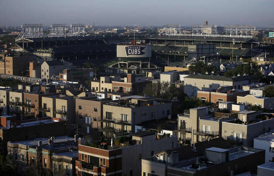 FILE - In this Oct. 7, 2016 file photo, Wrigley Field sits in the center of Wrigleyville neighborhood, in Chicago. Not since Oct. 10, 1945, has a World Series game been played at Wrigley Field in Chicago. As the World Series shifts to Chicago this weekend, all eyes are on the second-oldest ballpark in the major leagues. (AP Photo/Kiichiro Sato File)