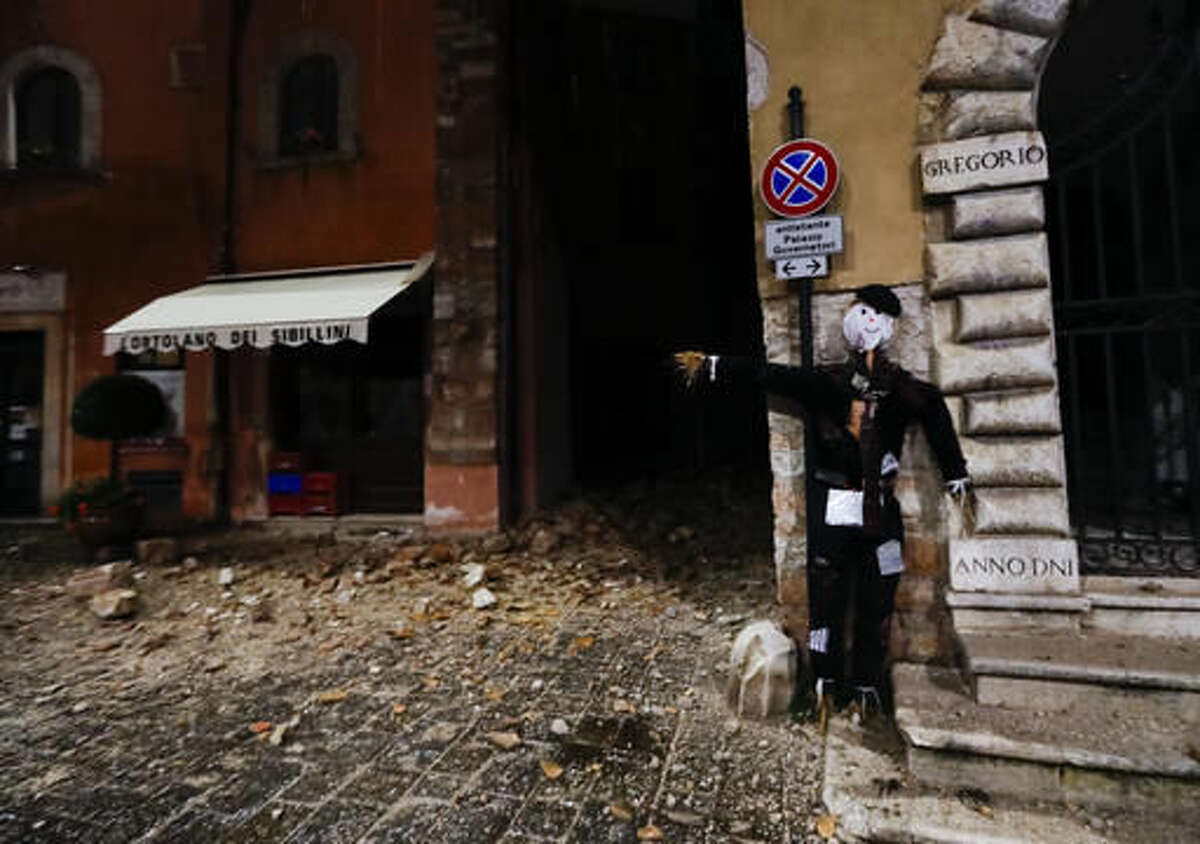 An Halloween dummy rests on a wall in the town of Visso in central Italy, early Thursday, Oct 27, 2016, after a 5.9 earthquake hit the area. A pair of strong aftershocks shook central Italy late Wednesday, crumbling churches and buildings, knocking out power and sending panicked residents into the rain-drenched streets just two months after a powerful earthquake killed nearly 300 people. (AP Photo/Alessandra Tarantino)