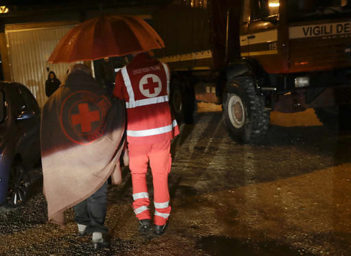 Residents of the small town of Visso in central Italy, early Thursday, Oct 27, 2016, are assisted by the Italian red Cross after a 5.9 earthquake destroyed part of their neighborhood. A pair of strong aftershocks shook central Italy late Wednesday, crumbling churches and buildings, knocking out power and sending panicked residents into the rain-drenched streets just two months after a powerful earthquake killed nearly 300 people. (AP Photo/Alessandra Tarantino)