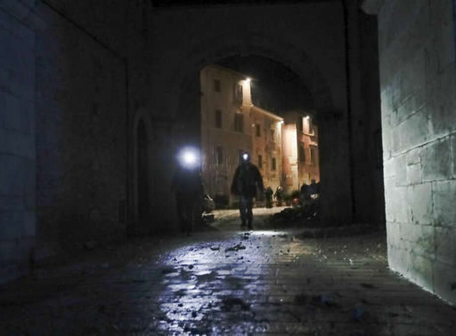 Rescuers and residents wander around the small town of Visso in central Italy under eavy rain, early Thursday, Oct 27, 2016, after a 5.9 earthquake that destroyed part of their neighborhood. A pair of strong aftershocks shook central Italy late Wednesday, crumbling churches and buildings, knocking out power and sending panicked residents into the rain-drenched streets just two months after a powerful earthquake killed nearly 300 people. (AP Photo/Alessandra Tarantino)