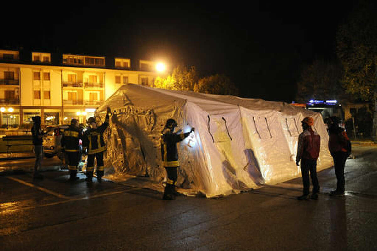 Rescuers set up tents in Ussita, central Italy, early Thursday, Oct 27, 2016, following an earthquake that destroyed part of the neighborhood. A pair of strong aftershocks shook central Italy late Wednesday, crumbling churches and buildings, knocking out power and sending panicked residents into the rain-drenched streets just two months after a powerful earthquake killed nearly 300 people. (AP Photo/Sandro Perozzi)